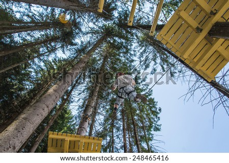 Man walking on a tightrope stretched in a rope park  - stock photo