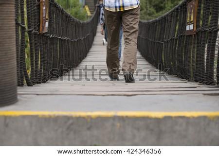 Man walking on a wooden bridge - stock photo