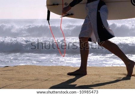 Man walking on beach with surfboard - stock photo