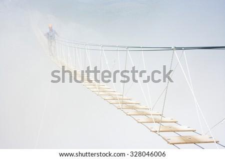 Man walking on hanging bridge in fog. - stock photo