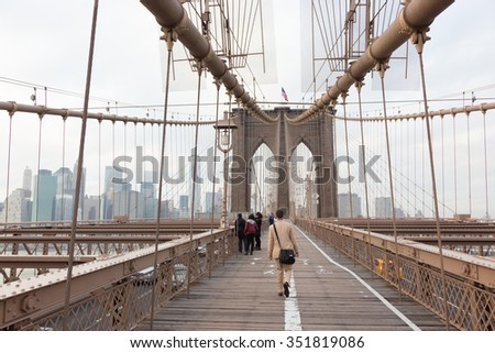 Man walking on pedestrian path across Brooklyn bridge. New York City Manhattan downtown with skyscrapers over East River panorama as seen from Brooklyn bridge. - stock photo