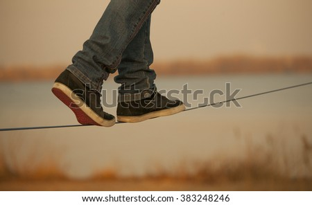 man walking on Slackline on the background of the river. Visible only  legs - stock photo