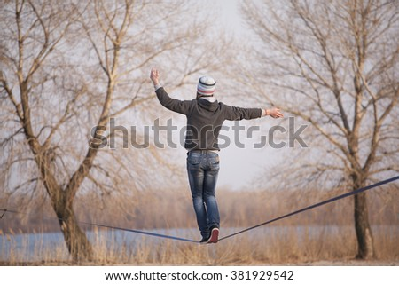 Man walking on slackline with river view in the park - stock photo