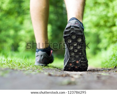 Man walking or running on trail in forest summer nature outdoors, sport shoes and exercising on footpath