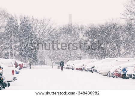 man walking through a snowy parking lot with snow falling on a winter day