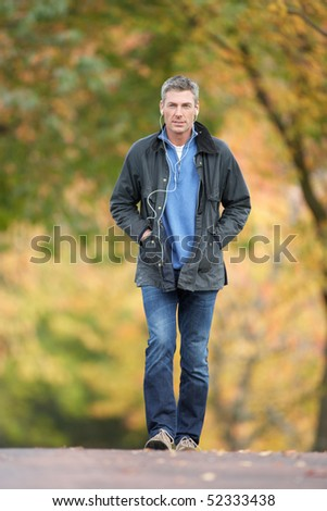Man Walking Through Autumn Park Listening to MP3 Player - stock photo