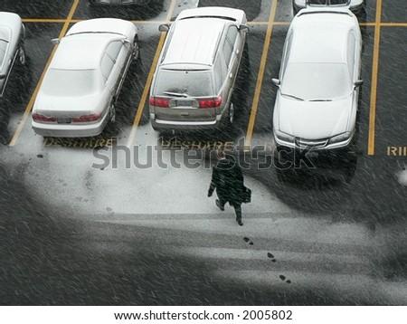 Man walking to car in snow. - stock photo