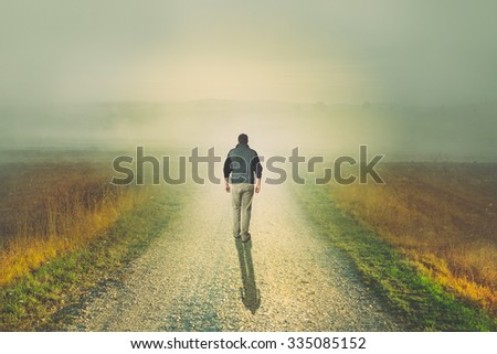 Man walking to the light on a foggy dirt road - stock photo