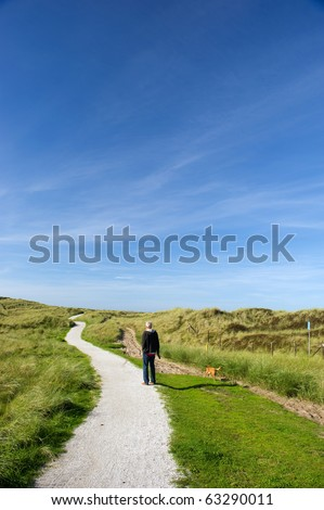 Man walking with dog in dunes at the coast - stock photo