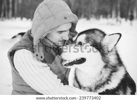 Man walking with dog winter time with snow in forest Malamute and Huskies friendship black and white - stock photo
