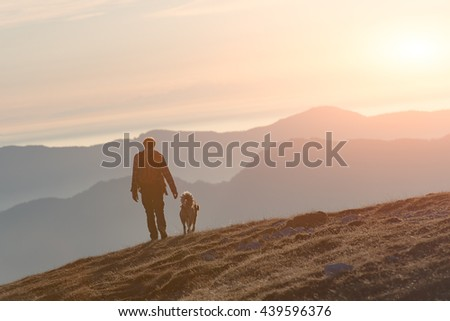 Man walking with his dog in the mountains around sunset - stock photo