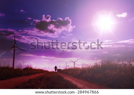 Man walking with his dog on the field with windmills. Beautiful nature background with setting sun and pink sky - stock photo