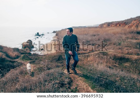 man walking with labrador dog on beach