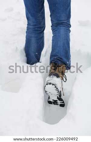 Man walks through the deep snow in a winter day. Foot in selective focus - stock photo