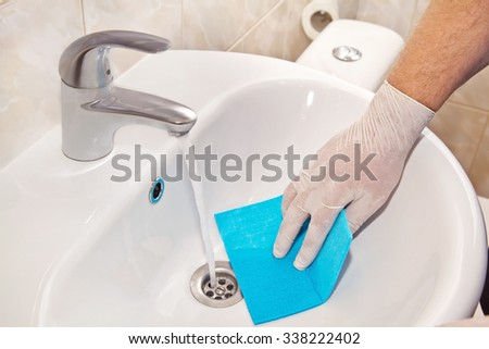 Man washes sink with a rag in his hand