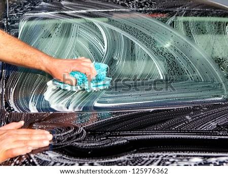 Man washing a black car with a cloth - stock photo