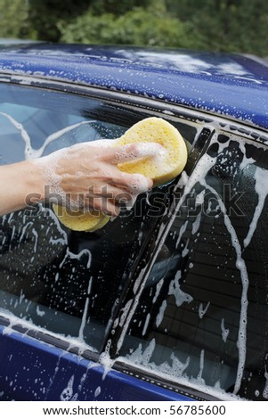 Man washing car with a soapy sponge. - stock photo
