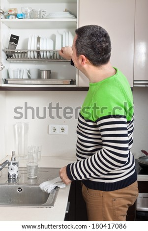 man washing dishes in  kitchen