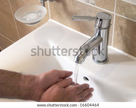 Man washing hands under running water in bathroom - stock photo