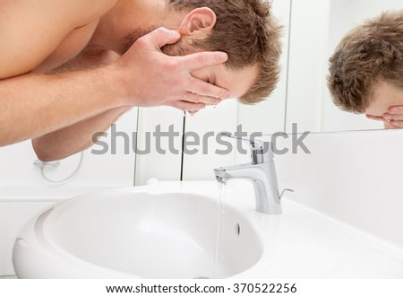 Man washing his face in the bathroom sink - stock photo