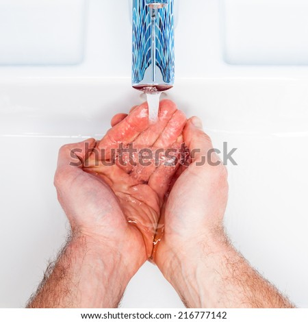Man washing his hands in a bathroom sink - stock photo