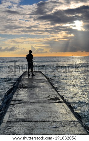 Man watching a sunset over the ocean on a jetty in Waikiki, Hawaii. - stock photo