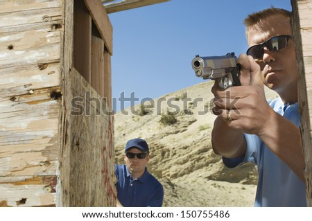 Man watching colleague aiming hand gun at firing range - stock photo