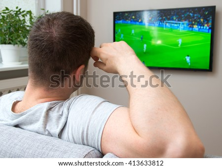 Man watching football match on television at home. - stock photo