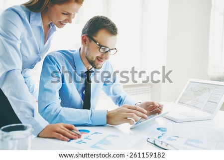 Man watching project of his colleague on digital tablet - stock photo