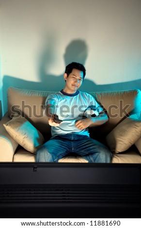 Man watching television late night - stock photo