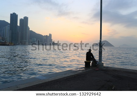 Man watching the far away sunset deep thinking in the pier waiting someone back,  with the part of Hong Kong island city, background of victoria harbour  - stock photo