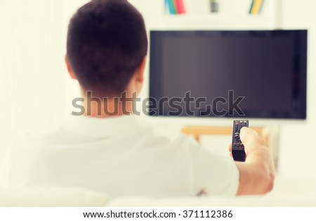 man watching tv and changing channels at home - stock photo