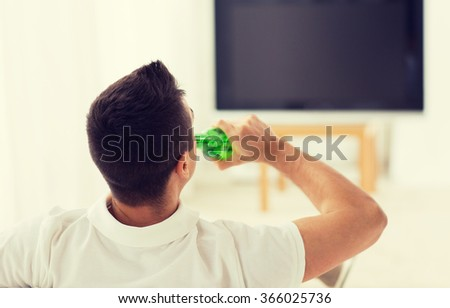 man watching tv and drinking beer at home - stock photo