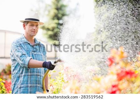 Man watering plants outside greenhouse - stock photo