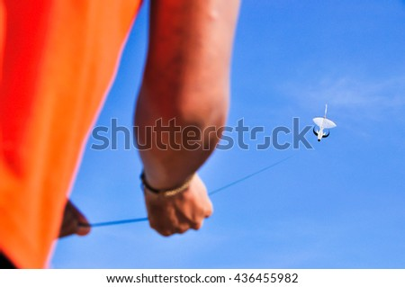Man wear orange shirt playing white kite on the sky, crop arm, left of frame, Thailand - stock photo