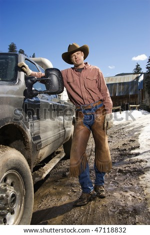 Man wearing a cowboy hat and leaning against a pickup truck. Vertical shot