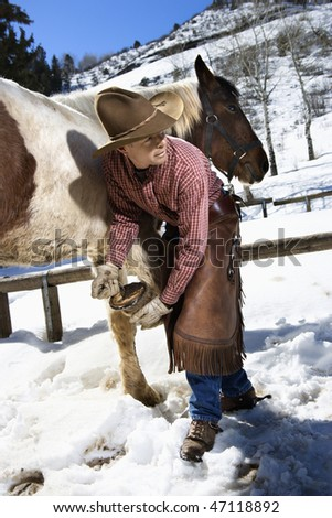 Man wearing a cowboy hat cleans out a horse hoof in the snow. Vertical shot. - stock photo