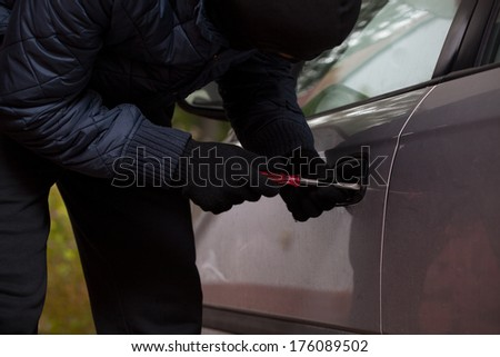 Man wearing a gloves tryng to break into the car