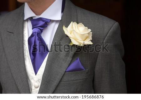 man wearing a rose buttonhole wedding flowers - stock photo