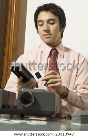 Man wearing a serious expression on his face as he looks at a slide next to a projector. Vertically framed photo. - stock photo