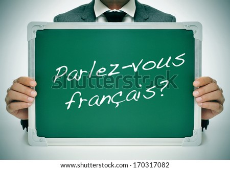 man wearing a suit holding a chalkboard with the question parlez-vous francais? do you speak french? written in it - stock photo