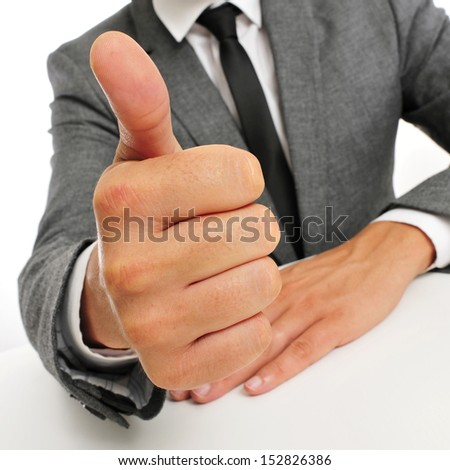 man wearing a suit sitting in a table giving a thumbs up signal - stock photo