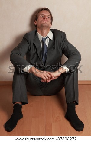 Man wearing a suit sitting on the floor looking tired