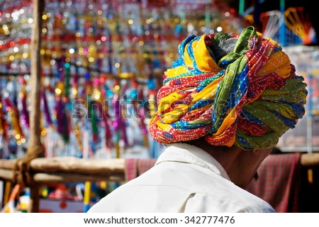 Man wearing a turban in a market place in India.  - stock photo