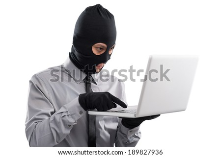 Man wearing balaclava searching for private information in the laptop