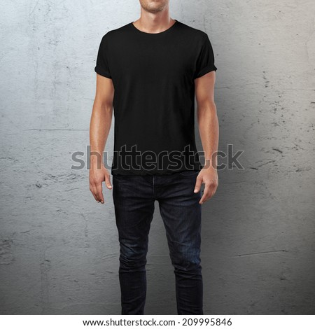 Man wearing black t-shirt. Concrete wall background - stock photo