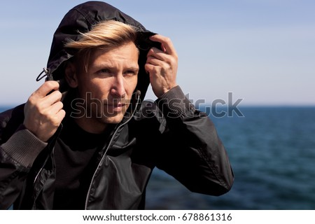 Man wearing black wind coat looking away on background of sea in sunny day.