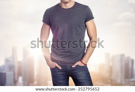 Man wearing blank t-shirt on blurred megalopolis background - stock photo