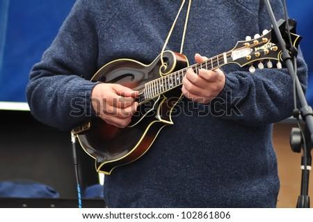 Man Wearing Blue Sweater Strumming a Mandolin - stock photo