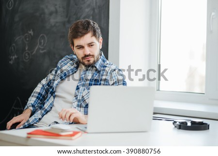 Man wearing casual clothes working at the office on laptop. College student thoughtful in study room - stock photo